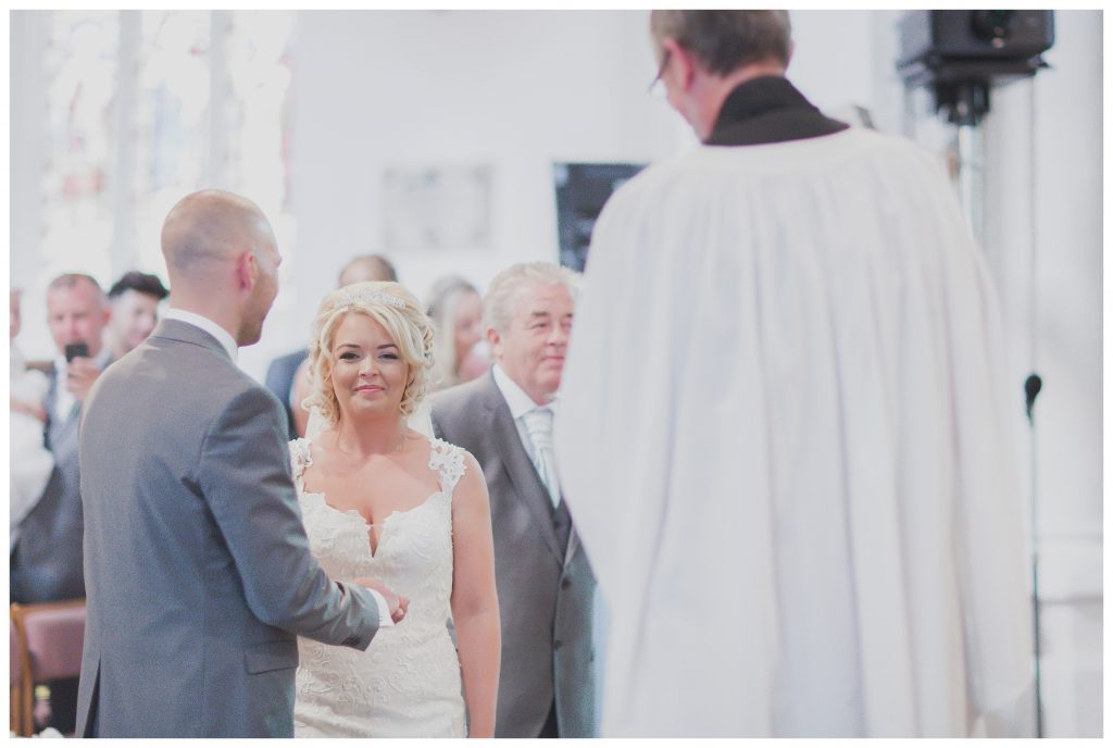Bride holding grroms hand at St Mary's church