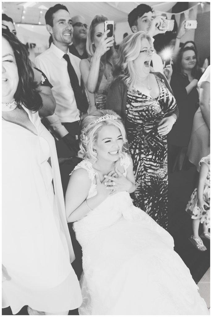 Bride laughing at grooms dancing