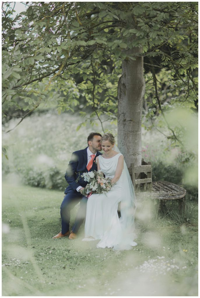 Brdie and groom sitting under a tree