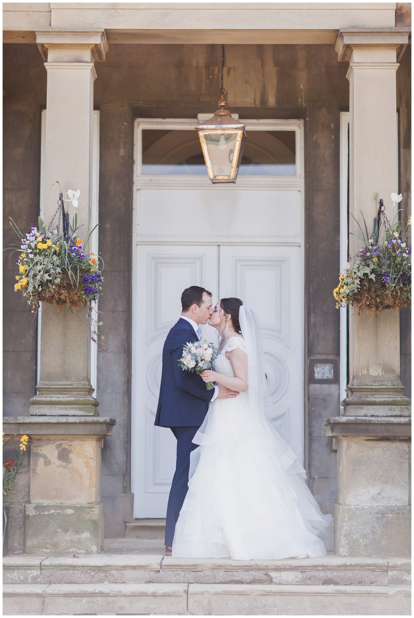 Bride and groom kissing at the entrance of Hothorpe Hall