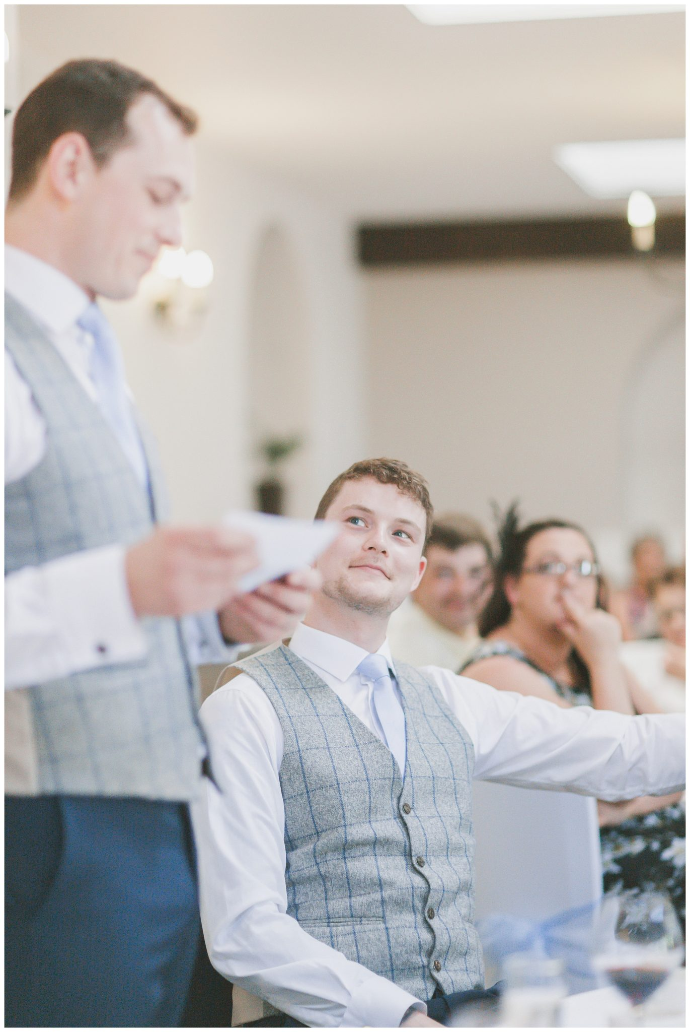 Best man looking at the groom during speeches.