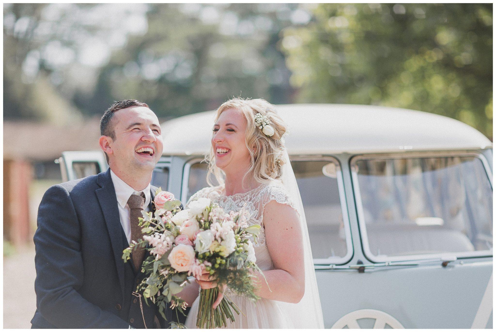 Bride and groom laughing by their VW van.