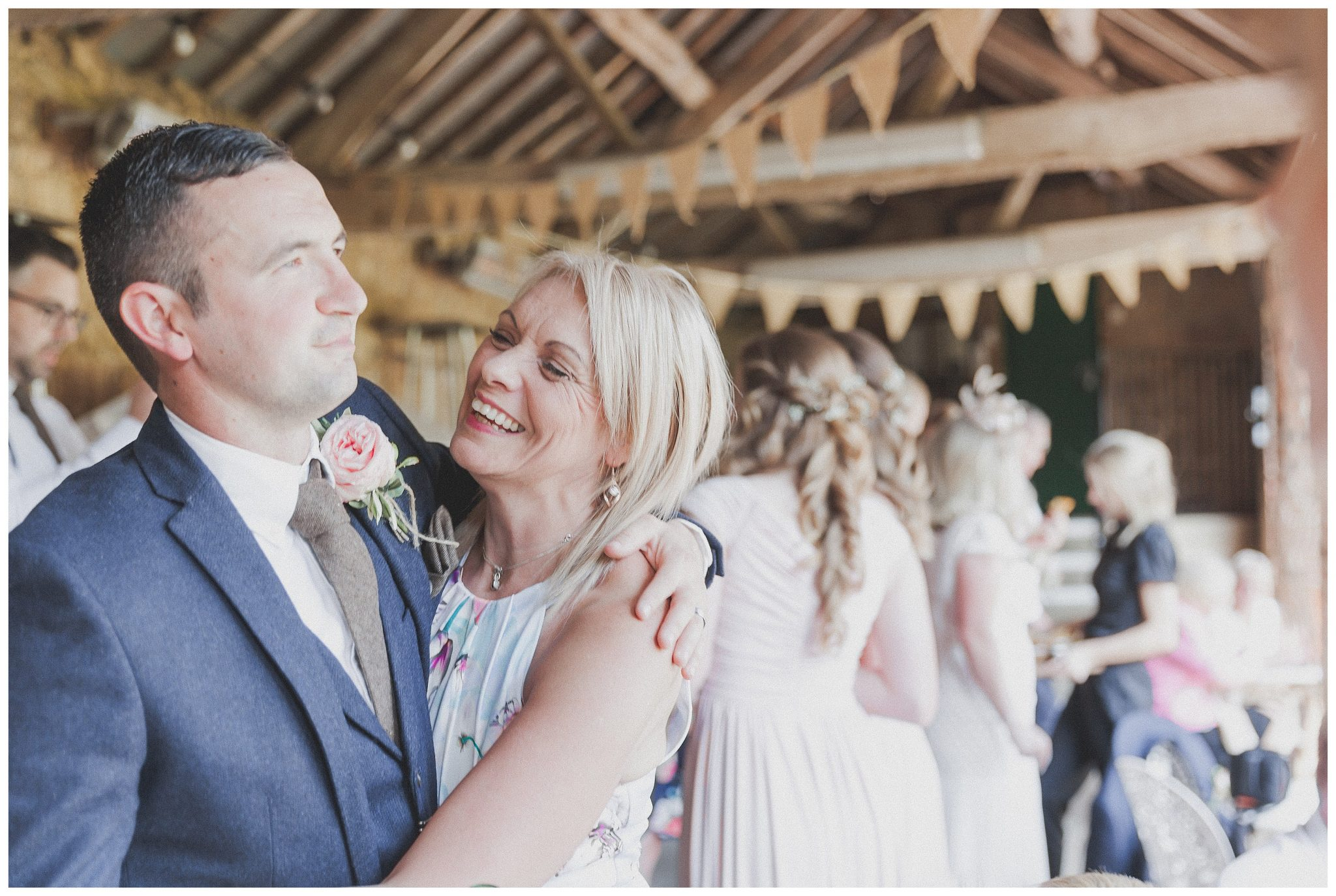 Groom laughing and hugging his mum
