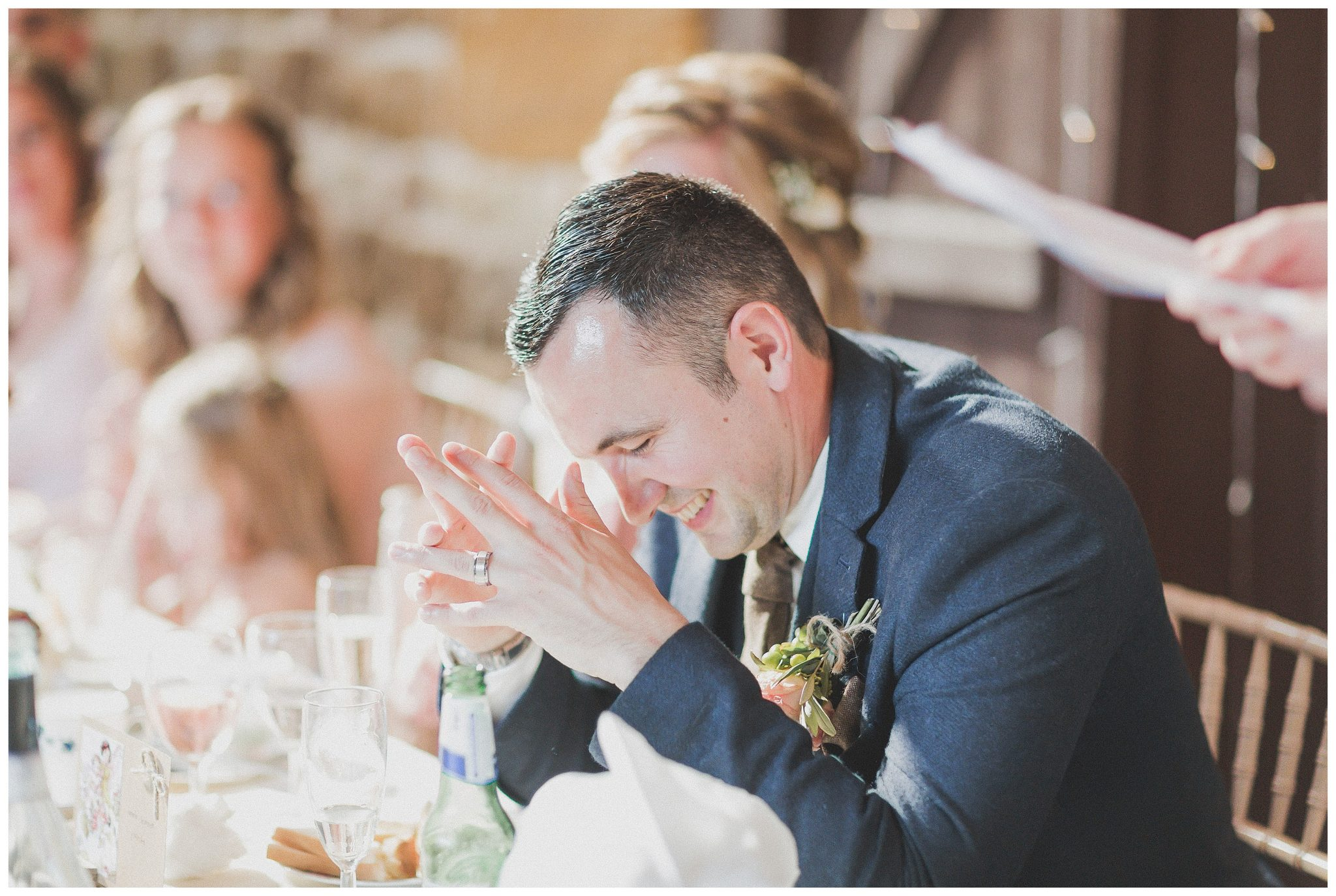 Groom laughing during bestman speech