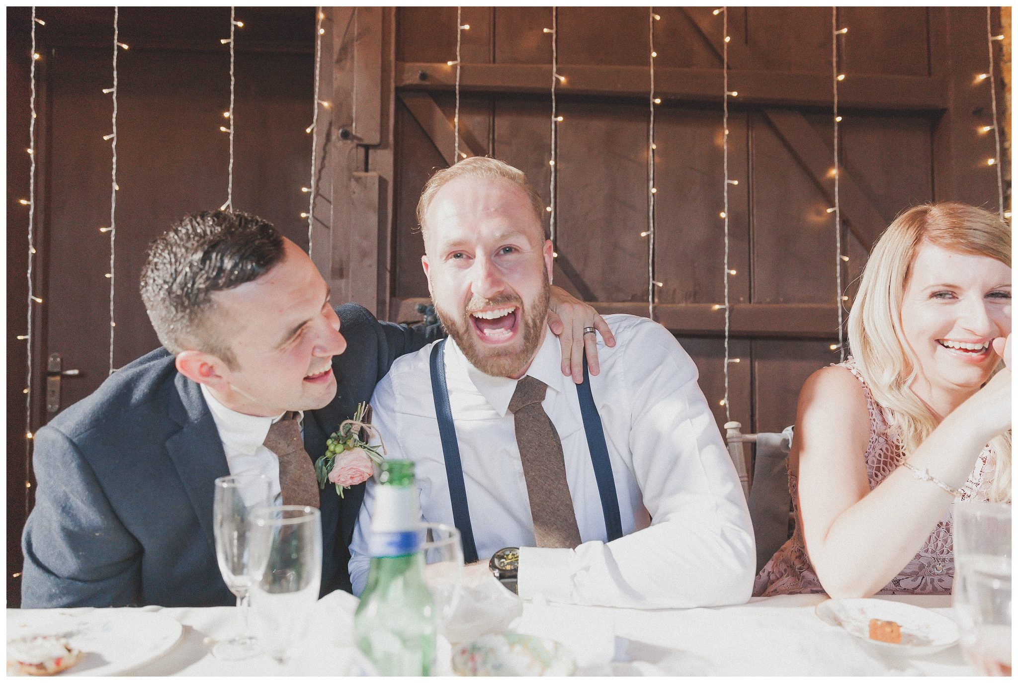 Groom and best man laughing together