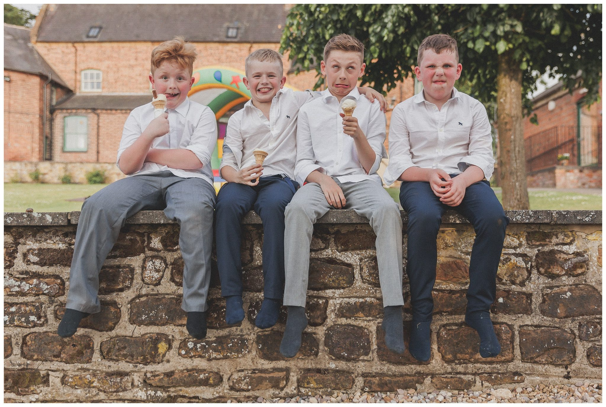 Boys sitting on a wall eating ice cream and pulling a silly face