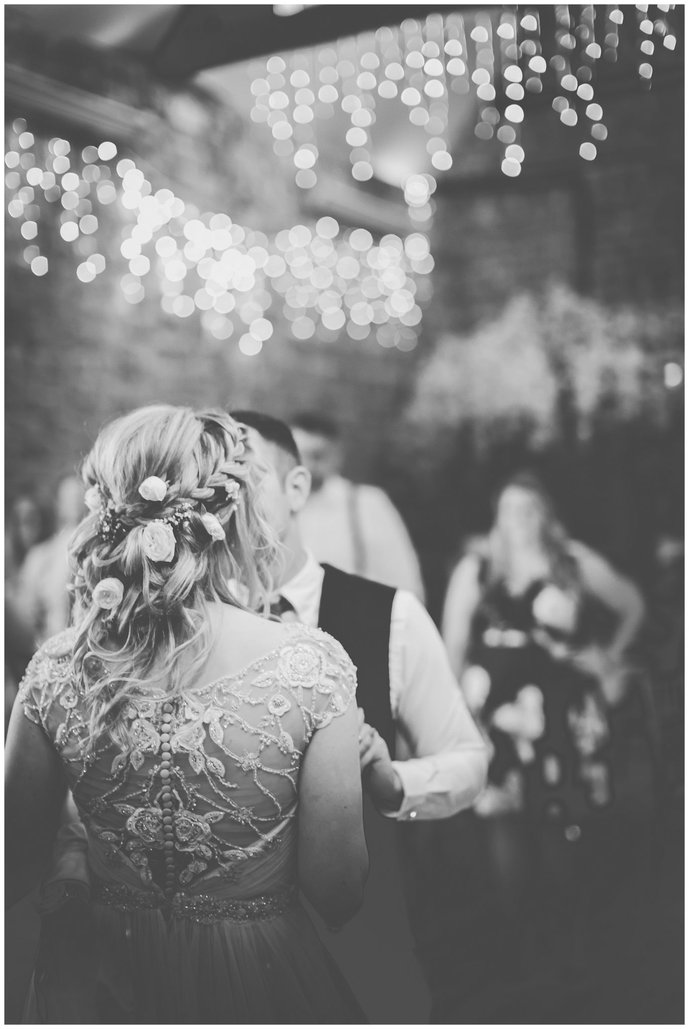 Black and white photo of the bride and groom dancing togehter