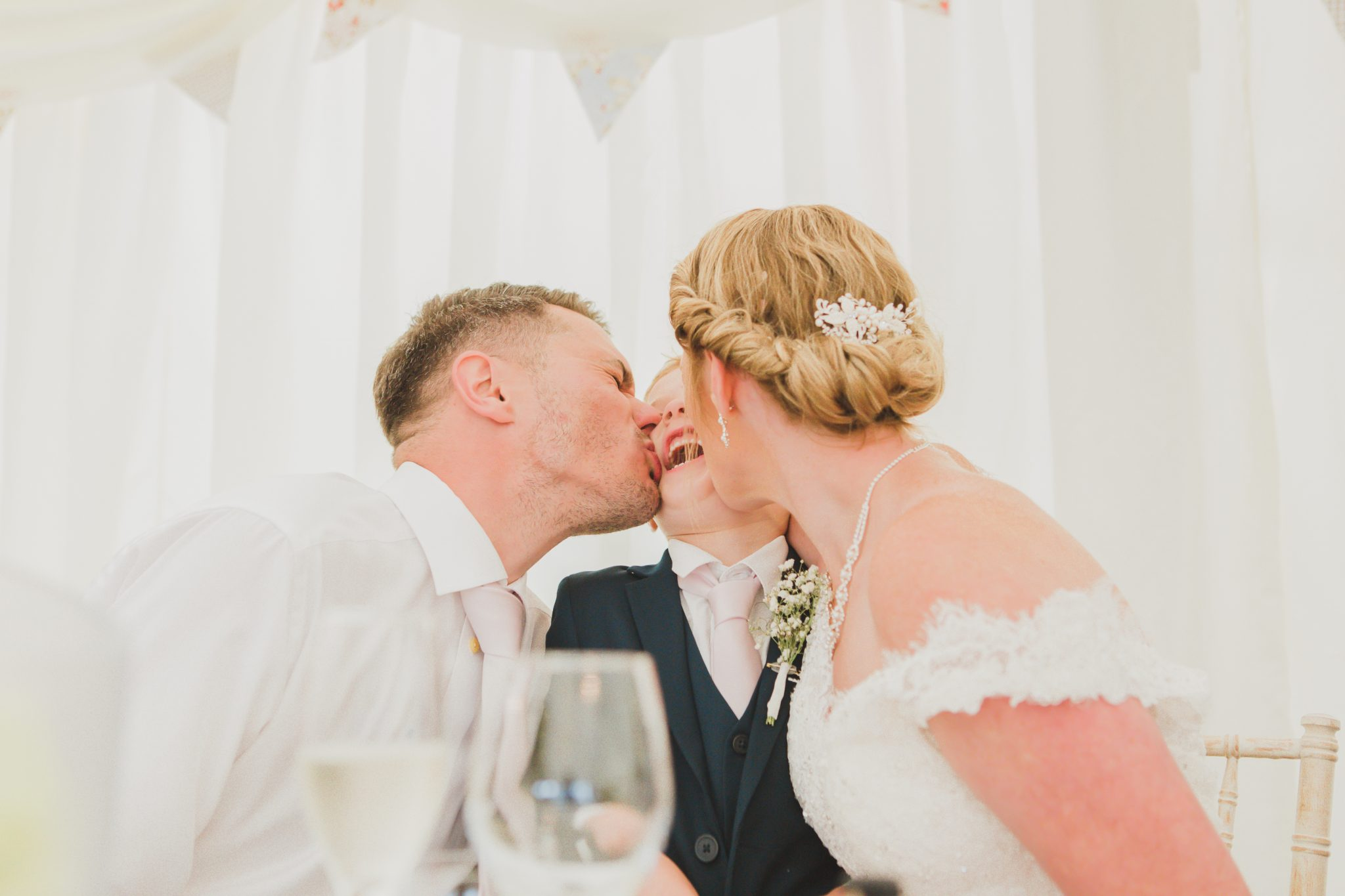 Bride and groom kissing their son