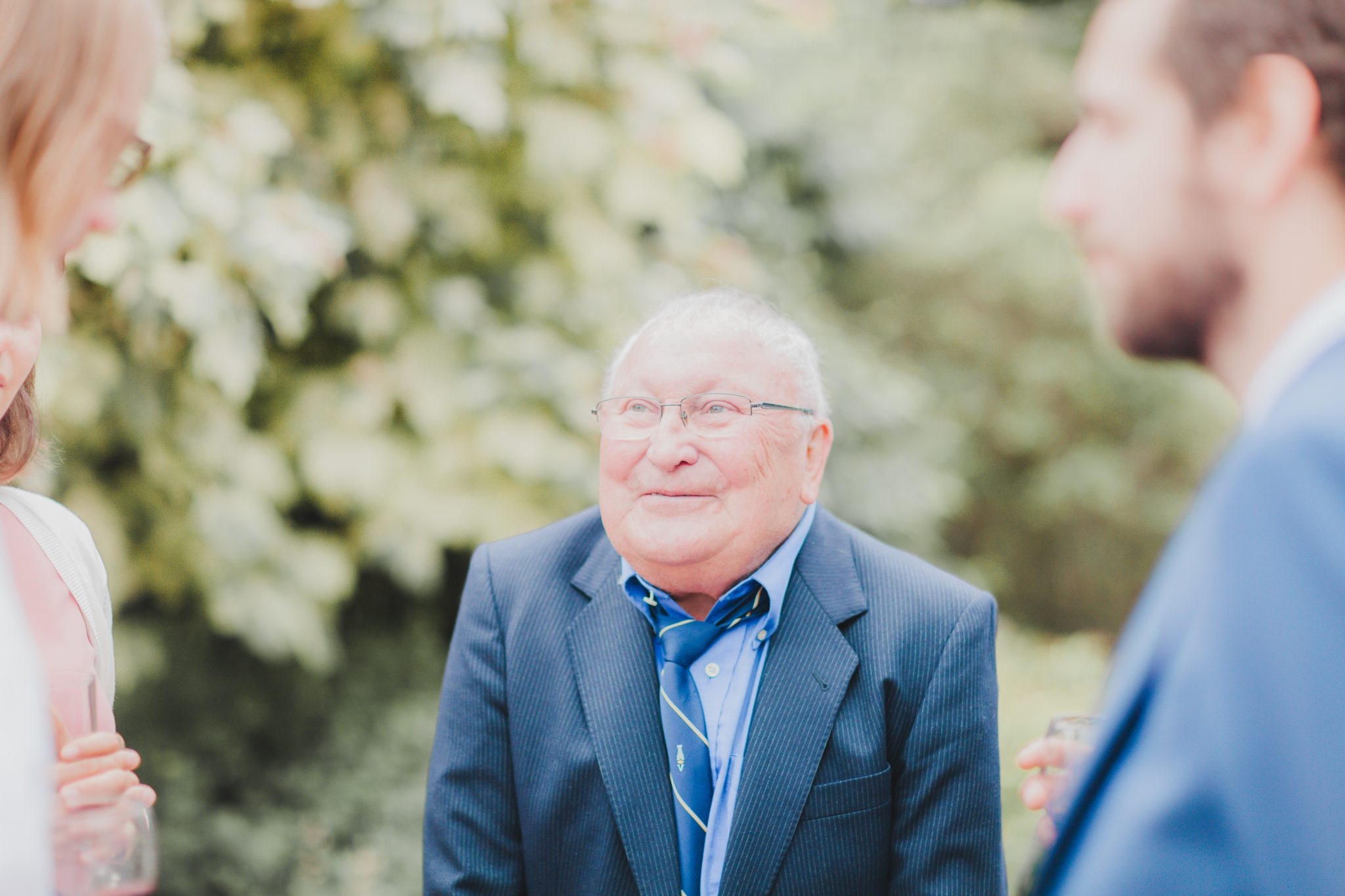 Granddad smiling at his grandchilds wedding day.