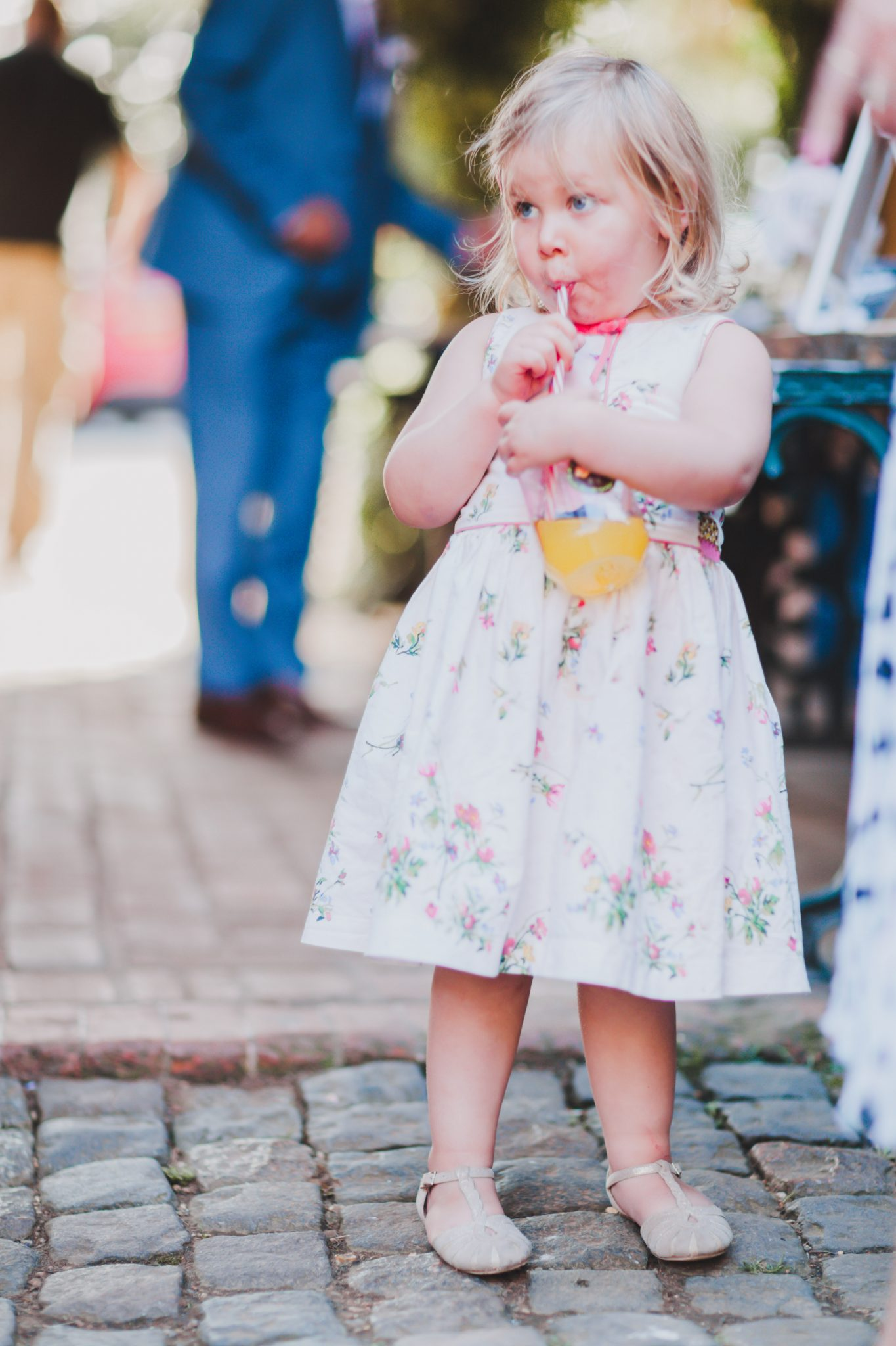 Little girl sipping drink from bottle at wedding